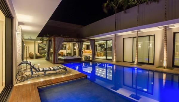 piscina central com iluminacao e deck de madeira