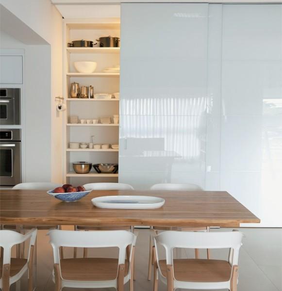 cozinha com mesa de madeira e armarios brancos