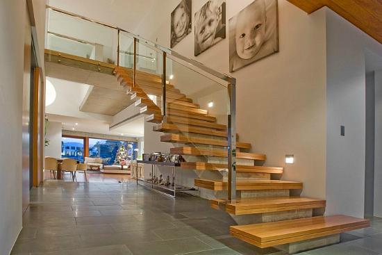 escada de concreto com degraus de madeira e guarda corpo de vidro