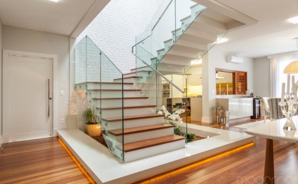 moderne arquitetura_escada silestone e madeira com destaque no primeiro degrau e guarda corpo de vidro